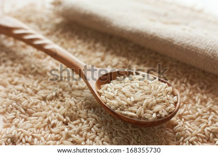 Uncooked brown  and wood spoon of rice - stock photo
