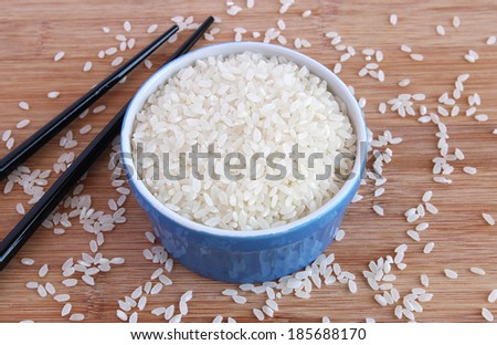 Uncooked calrose (sushi) rice in blue bowl with black chopsticks - stock photo