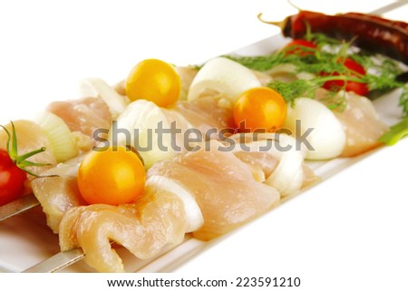 uncooked chicken shish kebab on long white - stock photo