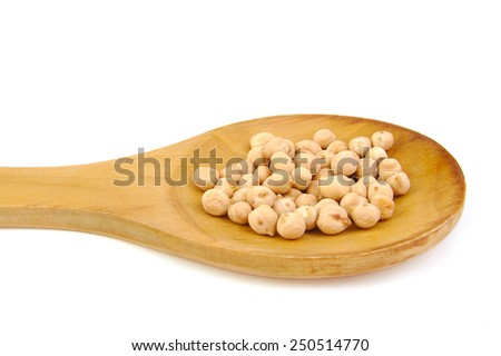 Uncooked chickpeas on wooden spoon on white background - stock photo