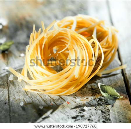 Uncooked coils of Italian linguine or tagliatelli pasta made from dried durum wheat dough on a grungy wooden table, square format - stock photo