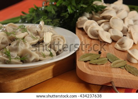 uncooked dumplings on a wooden cutting board with greens