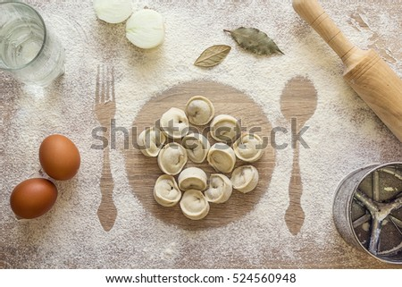 Uncooked dumplings, ravioli on the print plate in the flour, imprints fork and spoon, rolling pin, sieve, eggs, onion, glass and bay leaves on a wooden table. Dumpling recipe. Russian pelmeni.