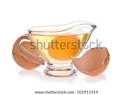 Uncooked egg in the glass and shells isolated on a white background - stock photo