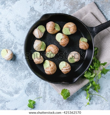 Uncooked Escargots de Bourgogne - Snails with herbs butter, gourmet dish, in black iron pan with parsley over blue textured background. Top view. Square image - stock photo