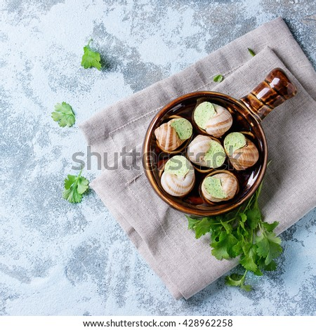 Uncooked Escargots de Bourgogne - Snails with herbs butter, gourmet dish, in traditional ceramic pan with parsley over blue textured background. Top view. With copy space. Square image - stock photo