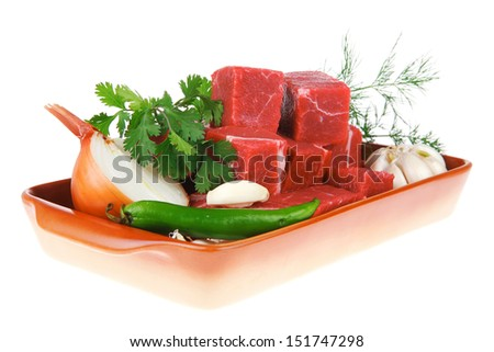 uncooked fresh beef meat chunks on ceramic bowls with vegetables and greenery isolated over white background - stock photo