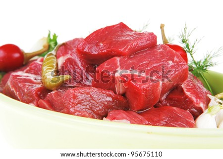 uncooked fresh beef meat chunks on ceramic bowls with vegetables and red peppers isolated over white background - stock photo