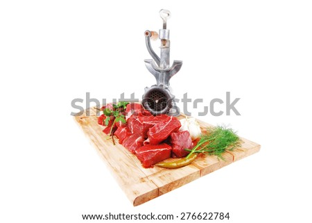 uncooked fresh beef meat chunks on wooden cutting plate with green hot and red peppers and grinder isolated over white background - stock photo