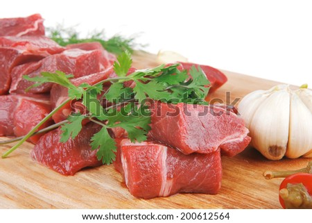 uncooked fresh beef meat chunks on wooden cutting plate with green hot and red peppers isolated over white background . shallow dof - stock photo