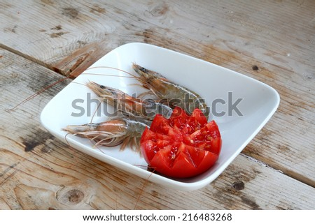 uncooked fresh raw shrimp on a white plate on a wooden base garnished with fresh red tomato - stock photo