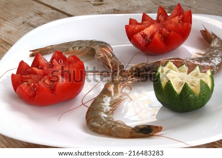 uncooked fresh raw shrimp on a white plate on a wooden base garnished with fresh red tomato