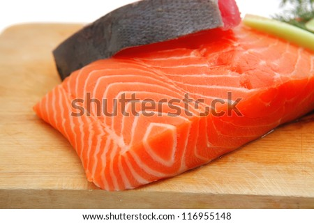 uncooked fresh salmon and red tuna fish pieces served over wooden board isolated on white background