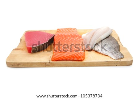 uncooked fresh sole , salmon , and red tuna fish pieces served over wooden board isolated on white background - stock photo