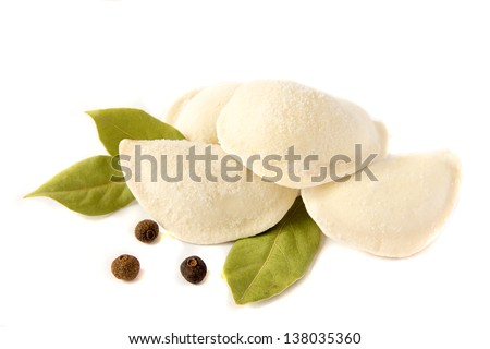 Uncooked frozen dumplings (russian traditional food - pelmeni) with pepper and bay leaf isolated on white background close up. - stock photo