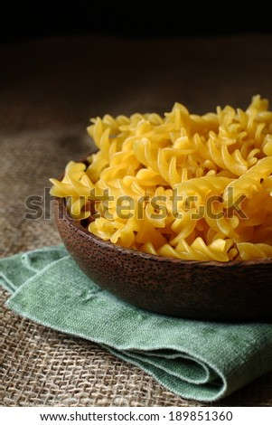 Uncooked gluten free fusilli pasta from blend of corn and rice flour in wooden bowl - stock photo