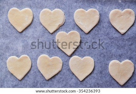 Uncooked heart shaped biscuits on a baking paper closeup