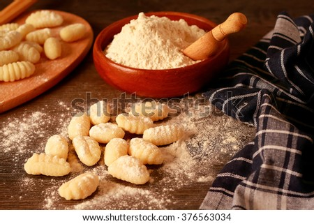 Uncooked homemade potato gnocchi on a rustic table - stock photo