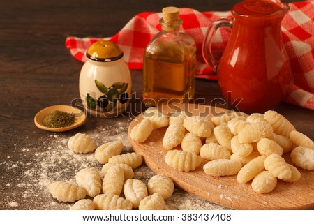 Uncooked homemade potato gnocchi on a rustic table with olive oil and tomato sauce - stock photo