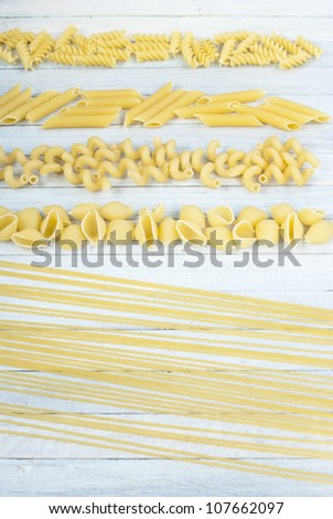 uncooked italian pasta, bright wood table background