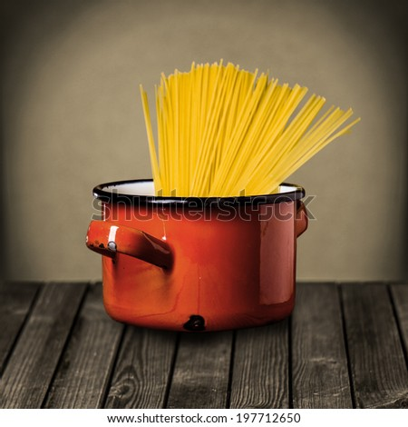 Uncooked Italian spaghetti in a colorful red enameled pot standing on a rustic wooden kitchen counter while preparing a tasty Italian pasta meal - stock photo
