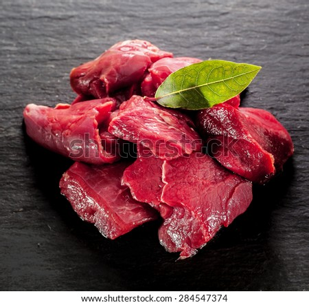 Uncooked lean healthy diced deer steak for a venison goulash with a bay leaf on a textured dark background, close up high angle - stock photo
