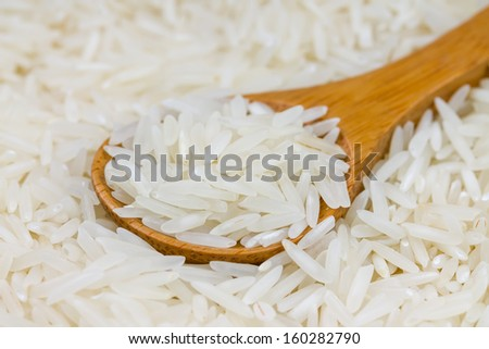 Uncooked long grain rice in a wooden spoon - stock photo
