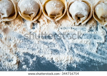 Uncooked meat dumplings lies on a flour and blue table - stock photo