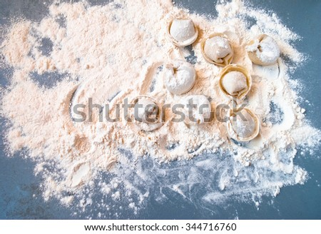 Uncooked meat dumplings lies on one part of the blue table - stock photo