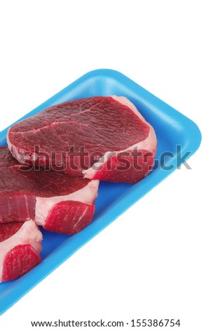 uncooked meat : raw fresh beef pork tenderloin strip ready to cooking on blue tray isolated over white background
