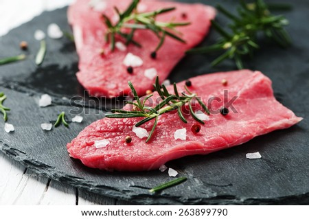 Uncooked meat with rosemary and salt, selective focus - stock photo