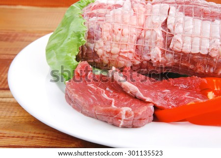 uncooked meat with vegetables on wooden table