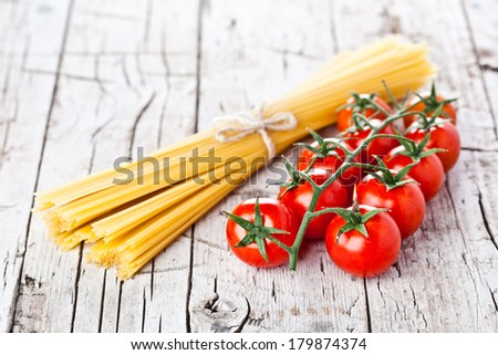 uncooked pasta and fresh tomatoes on rustic wooden background  - stock photo