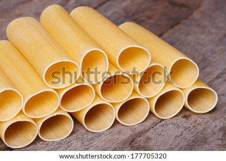 Uncooked pasta cannelloni on an old wooden board. closeup horizontal  - stock photo