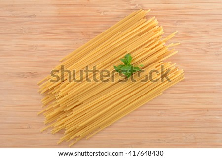 uncooked pasta noodles on butcher block background - stock photo