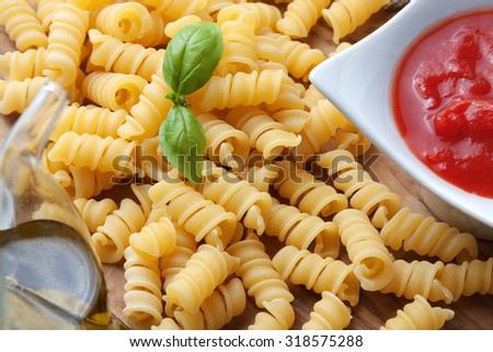 uncooked pasta on a wooden table, with basil and tomato sauce - stock photo