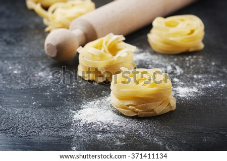 Uncooked pasta with flour on the table, selective focus - stock photo
