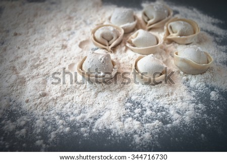 Uncooked pelmeni on a blue wooden table - stock photo