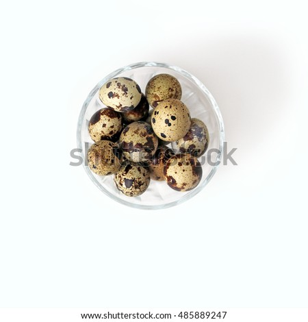 Uncooked Quail eggs in transparent bowl on white background top view, healthy food concept
