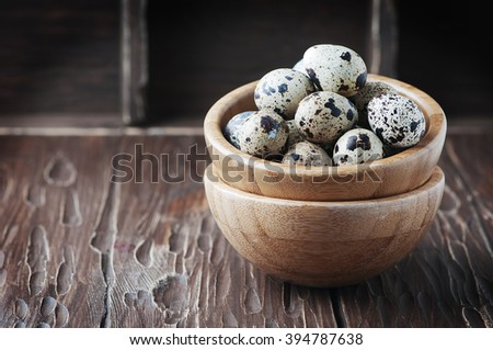 Uncooked quail eggs on the wooden table, selective focus - stock photo