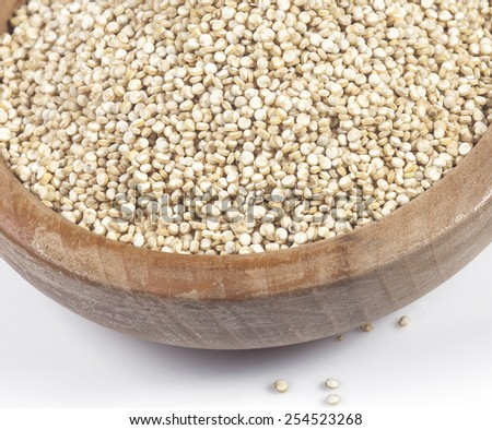 Uncooked quinoa in the wooden bowl. Macro image with selective focus. - stock photo