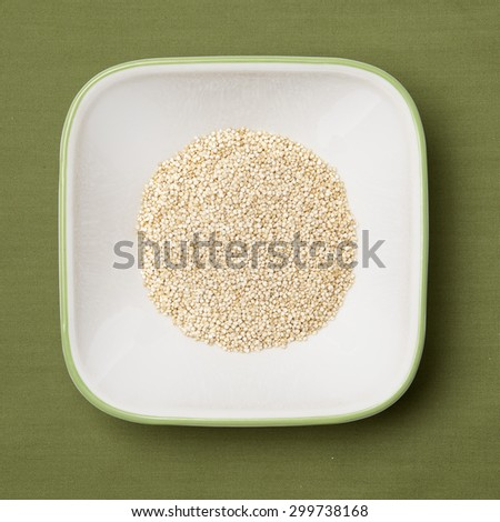 Uncooked quinoa in white bowl, green background - stock photo