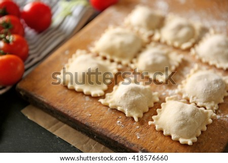 Uncooked ravioli on cutting board - stock photo