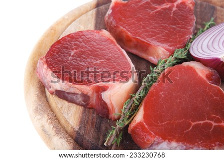 uncooked raw beef fillet with thyme twig on wooden plate isolated over white background - stock photo