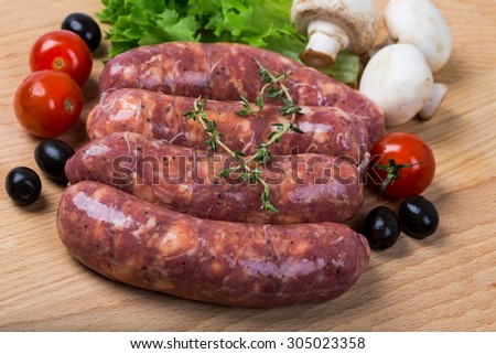 uncooked raw sausages with lettuce, tomatoes, mushrooms on wooden board - stock photo