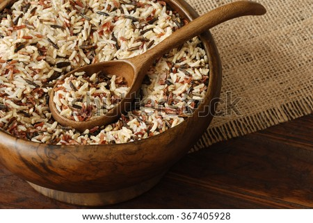 Uncooked rice blend (wild, brown, red, and white ) in vintage, handcrafted bowl on rustic wood background.  Closeup with shallow dof.   - stock photo