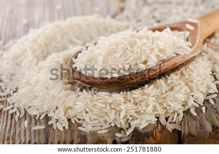 Uncooked rice in a wooden  spoon . Selective focus - stock photo