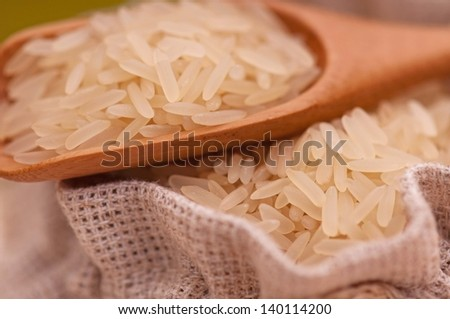 Uncooked rice in bamboo spoon on a burlap bag close-up - stock photo