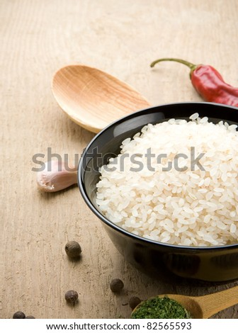 uncooked rice in bowl with spoon on wood background - stock photo