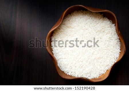 Uncooked rice in wooden bowl - stock photo